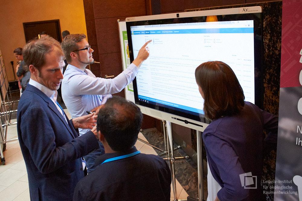 Teilnehmer/-innen im Gespräch vor einem Monitor